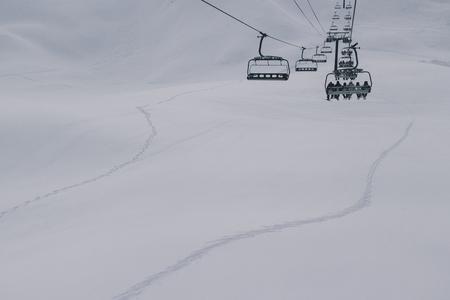 People on a ski lift on a foggy day. La Plagne, France. Imagens