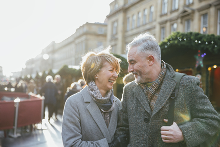 A mature married couple are walking through a Christmas market together.