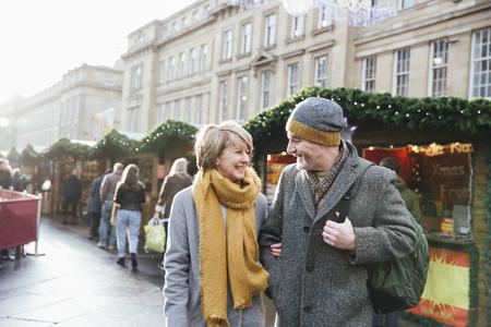 성숙한 결혼 한 커플 함께 크리스마스 시장을 걷고있다. 스톡 콘텐츠