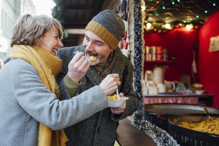 成熟したカップルはクリスマス市場の屋台からいくつかのパエリヤを共有を楽しんでいます。