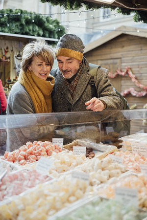 Mature couple are choosing which turkish delight to buy at a christmas market.