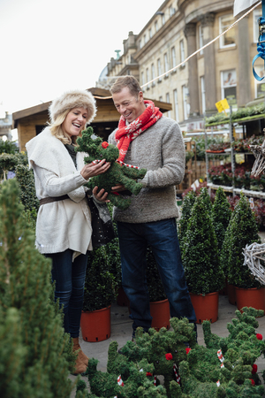 Mature couple are enjoying buying christmas decorations in the town christmas market.