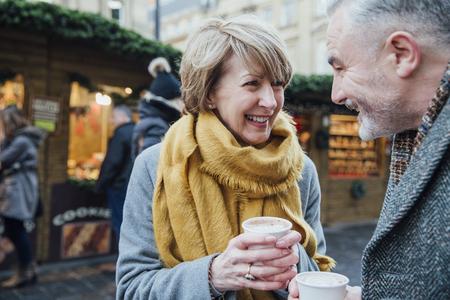 Ouder paar geniet van een kopje koffie terwijl ze de kerstmarkt van de stad verkennen. Stockfoto