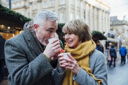 成熟したカップルは街のクリスマス マーケットでホットド リンクを飲んでいます。