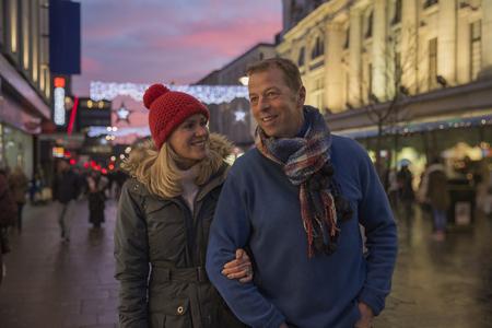 成熟したカップルは、クリスマスの時期に町を通って夜の散歩を楽しんでいます。 写真素材