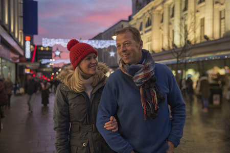 Mature couple are enjoying an evening stroll through town at Christmas time.