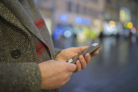Close up of males hands texting on mobile phone outdoors on the highstreet during winter. Stock Photo