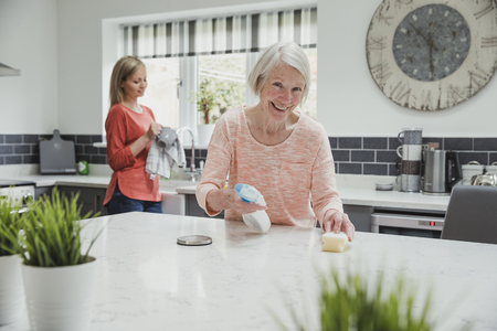 Senior woman is smiling for the camera as she cleans her kitchen with help from her daughter.