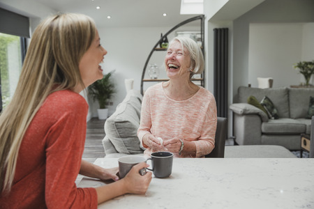 Senior woman is enjoying a catch up with her daughter. They are sitting in the kitchen drinking cups of tea.