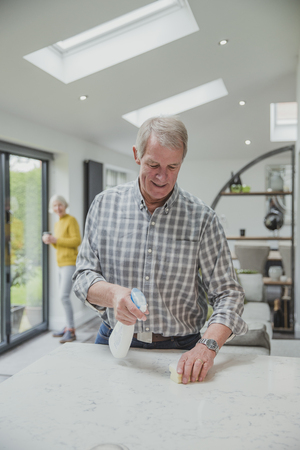 Senior man is cleaning the kitchen of his home with his wife, who can be seen in the background.  Stok Fotoğraf