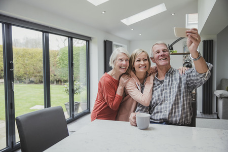 Happy family are taking a selfie using a smart phone.