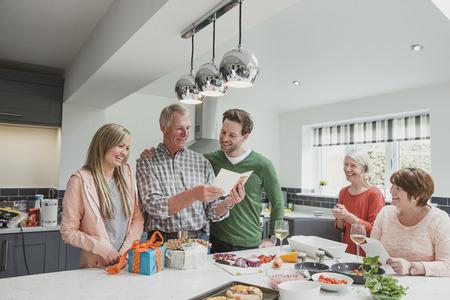 가족은 부엌에서 함께 식사를 요리하고 있습니다. 두 자녀는 어머니와 아줌마가 지켜 보는 동안 생일 카드와 선물을 가진 그들의 아버지를 놀라게합니