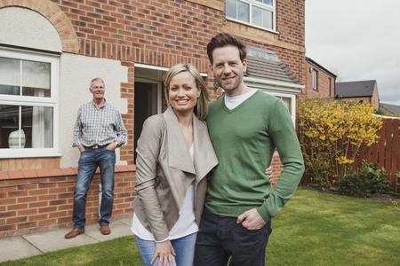 Trotse vader kijkt toe terwijl zijn zoon een foto maakt met zijn vrouw en hun nieuwe eerste huis.