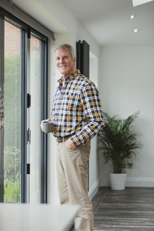 Portrait of a senior man in his home. He is standing by the patio doors with a cup of tea and is smiling for the camera. Stock Photo