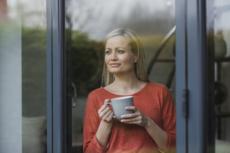 Woman is standing at the window of her home, enjoying a cup of tea.