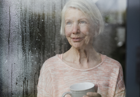 Senior woman is watching the rain from a window in her home while enjoying a cup of tea.