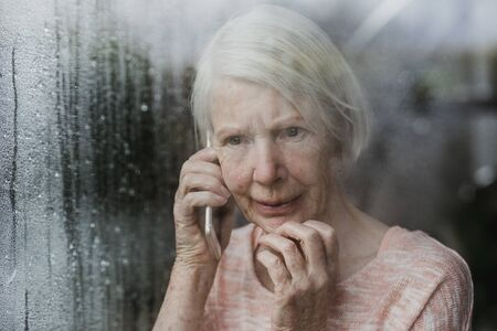 Senior woman is looking worriedly out of the window of her home while talking to someone on the phone. Stockfoto