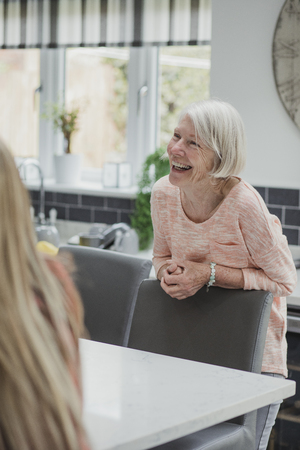 Senior woman is enjoying some catch up time with her daughter in the kitchen of her home.