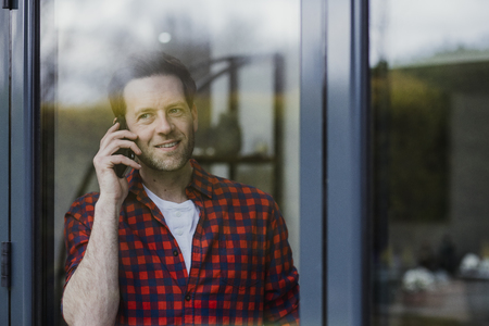 Man is looking out of a window in his home while talking to someone on the phone. Stock Photo