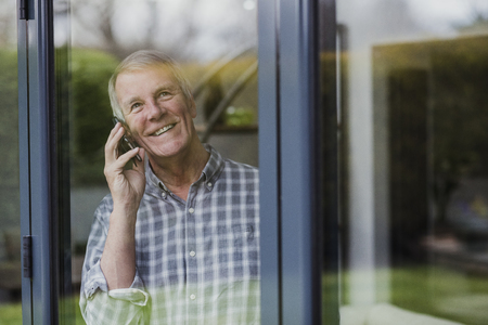 Senior man is enjoying a phone call while he looks out of a window in his home.