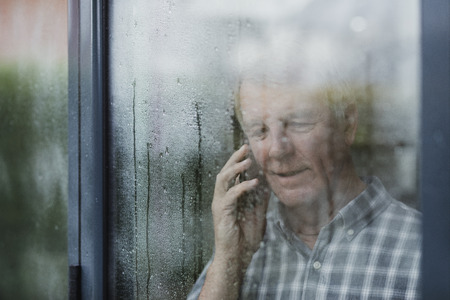 Senior man is talking to someone on the phone in his home. He is standing at the window and it is raining outside.  Stock Photo