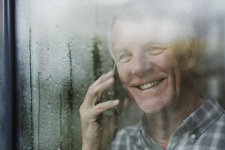 Happy senior man is watching the rain from his window while talking to someone on the phone.