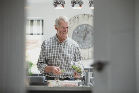 Happy senior man is preparing a meal in the ktichen of his home. He is taking rocket out of the bag and placing it in a bowl.
