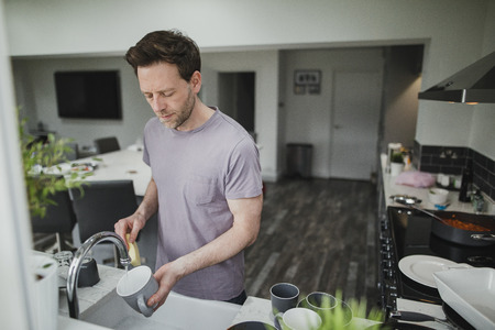 Man is washing the dishes in the kitchen of his home.