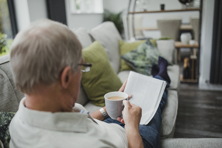 Over the shoulder shot of a senior man reading a newspaper while enjoying a cup of tea, with his feet up on the sofa. Stock Photo