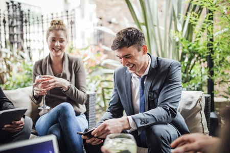 Businessman is enjoying drinks in a bar courtyard with colleagues. He is laughing while using his smart phone.  Stock Photo