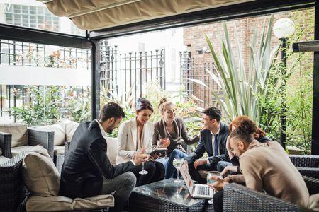 ビジネス人々 のグループは、バーで自分の仕事を論議している作業後の中庭。カクテルを飲み、技術を使用しています。 写真素材