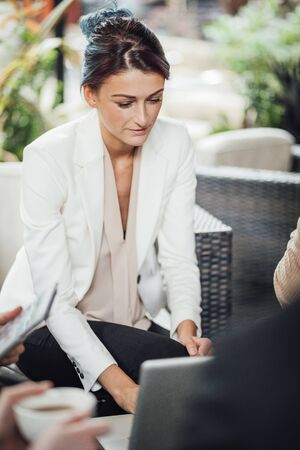 Close up shot of a business woman working on a laptop in a business meeting. It is taking place in a bar courtyard. Stock Photo