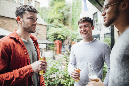 Three men are enjoying drinks together in the courtyard of a bar. They are talking and drinking bottles of beer.  Stockfoto