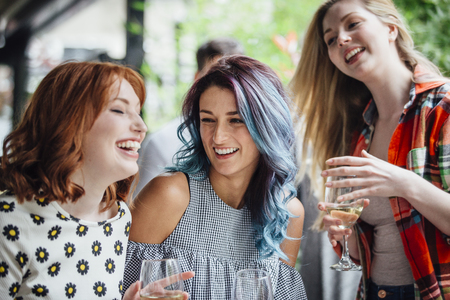 Three women are talking while enjoying drinks in a bar courtyard. They are laughing and drinking wine. Stock Photo