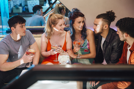 Friends are enjoying drinks in a nightclub together. They are talking while sitting at a table in the lounge area.  Фото со стока