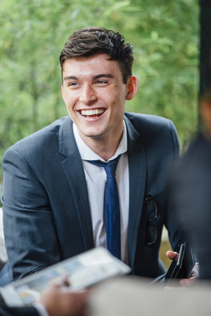 Close up shot of a business man laughing while talking to someone in a business meeting. They are in the outdoor seating area of a cafe.  Stock Photo