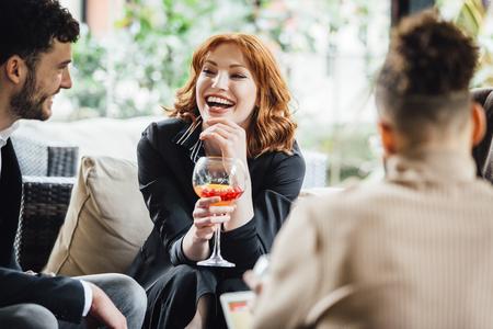ビジネスの人々 はバーで飲み物を一緒に楽しんでいる仕事の後シティビュー。彼らは笑って、カクテルを飲みながら話しています。