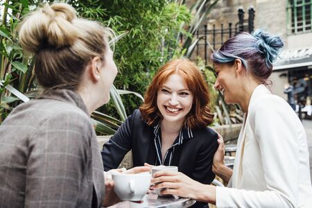 Three business women are enjoying a coffee break together in the city. They are sitting in the outdoor area of a cafe and are all laughing and talking together,  Stock Photo