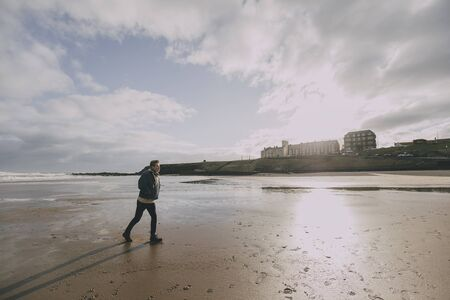 A young man walks alone on a winter beach in Tynemouth. Stock Photo