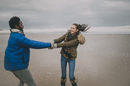 A young couple laugh and dance on Tynemouth beach in winter.