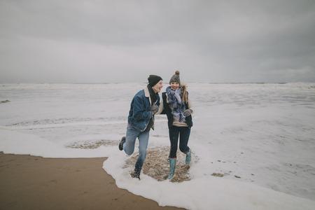 젊은 부부 웃음과 겨울 해변에서 바다에서 헤 엄. 스톡 콘텐츠