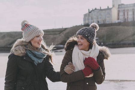 Two women laughing on a winter beach.