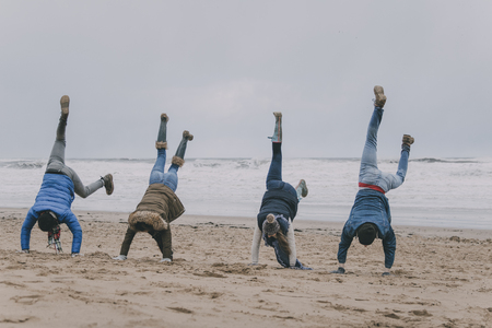 A group of teenagers have fun on a winter beach doing handstands.
