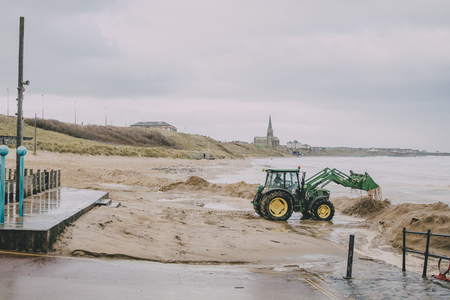 Ein Traktor gräbt im Sand auf Tynemouth-Strand im Winter. Standard-Bild - 86471567