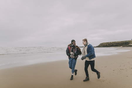 Two friends talk and laugh whilst walking along a winter beach.
