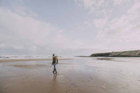A young woman walks alone on a winter beach in Tynemouth whilst facing away from the camera.