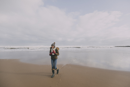 A young woman walks alone along a winter beach in Tynemouth whilst smiling.