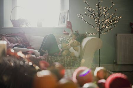 Little girls are lying down after a busy christmas morning. One is wearing christmas antlers and cuddling teddybears.