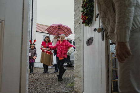 Excited family arriving at their grandmothers house at christmas time.