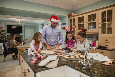 Little girls are making christmas biscuits at home with their father. The mother can be seen writing out christmas cards in the background.